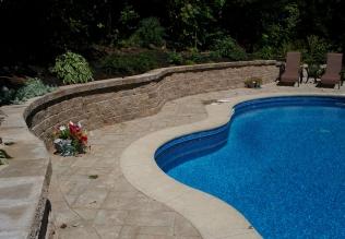 Muret de pierre en contour de piscine réalisé par Pavé Design à l'aide de blocs Permacon
