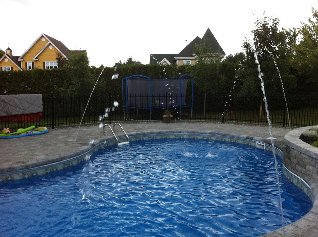 Contour de piscine creusée avec des blocs Permacon et décoré avec des jets d'eau