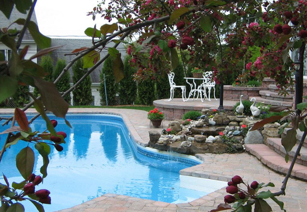 Contour de piscine réalisé avec des blocs Permacon et agrémenté d'un jardin