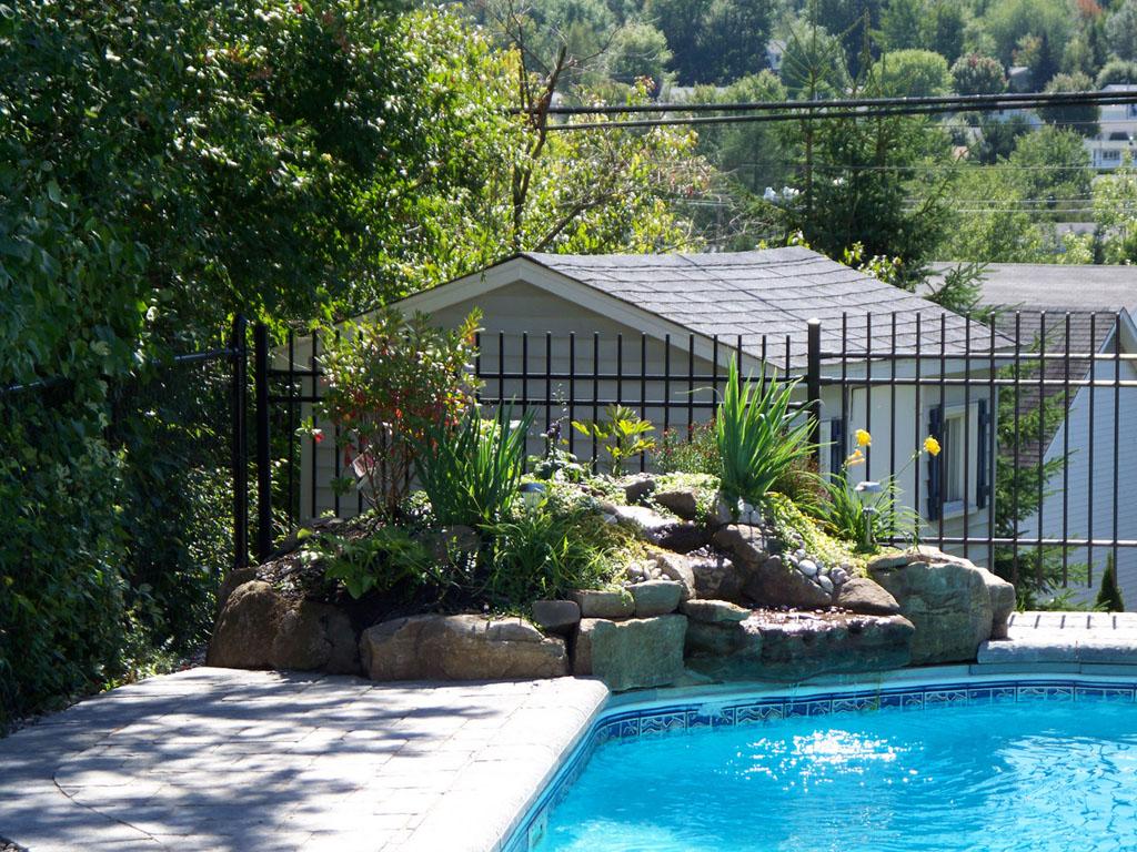 Contour de piscine creusé dans un espace clôturé et réalisé à partir de blocs Permacon