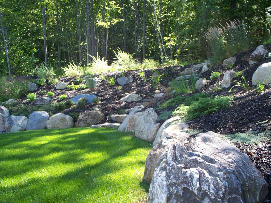 Terrassement stylisé réalisé avec l'aide de pierres et de végétation